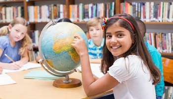 44788175-cute-pupils-looking-at-globe-in-library-at-the-elementary-school