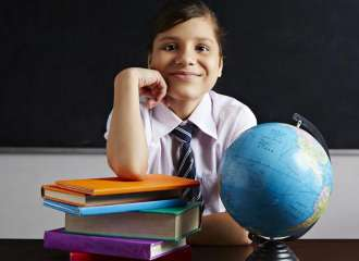 Portrait of a school girl sitting in front of a blackboard with books and a globe
